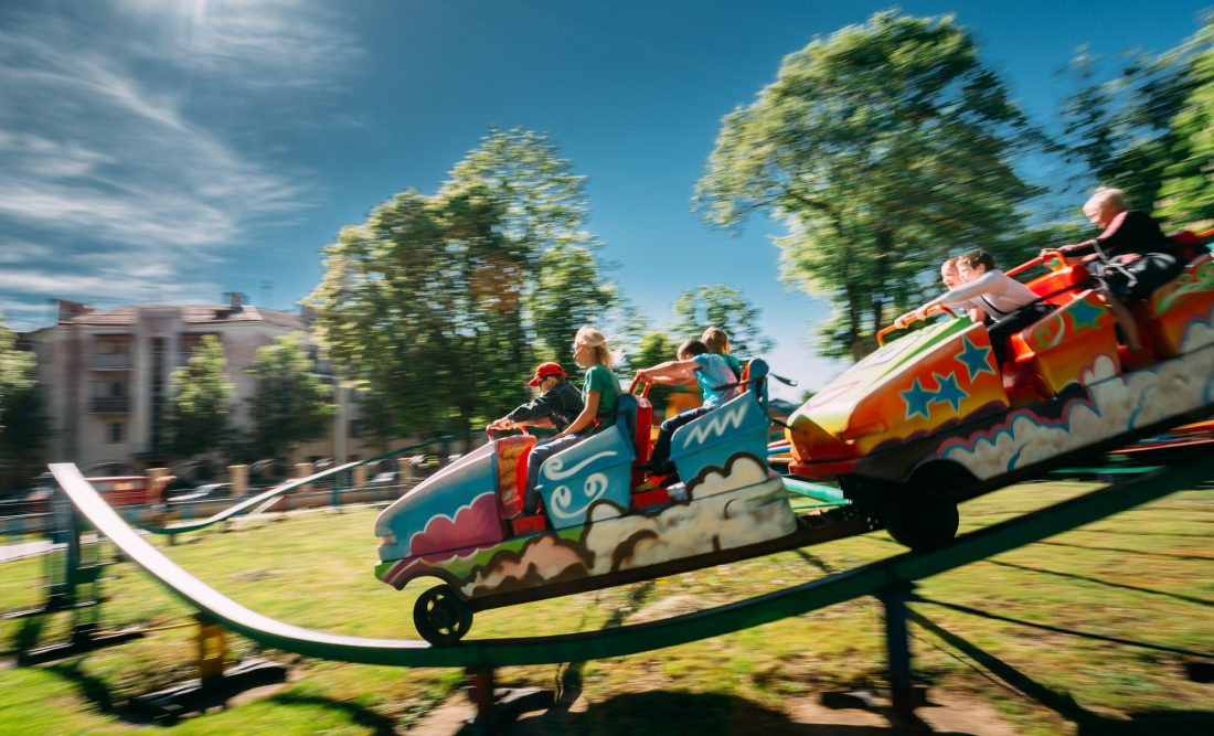People Having Fun On Rollercoaster In Park. Photo With Zoom Blur