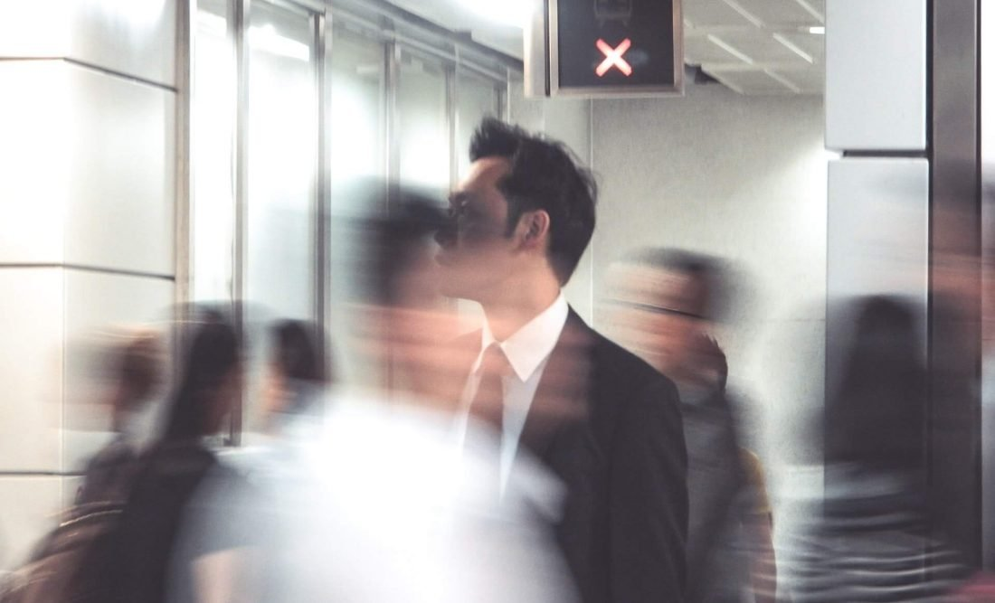 Business man with blurred travellers