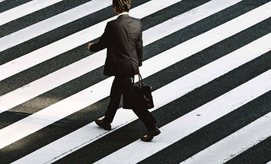 Image of business man walking on zebra crossing