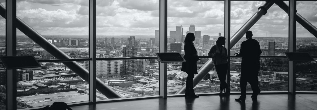 Business people in high rise building looking at view